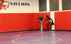 Junior Dominik Bishop mops the mats before wrestling practice begins.