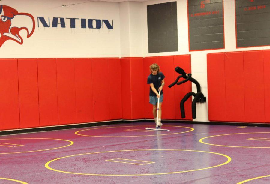 Junior+Dominik+Bishop+mops+the+mats+before+wrestling+practice+begins.