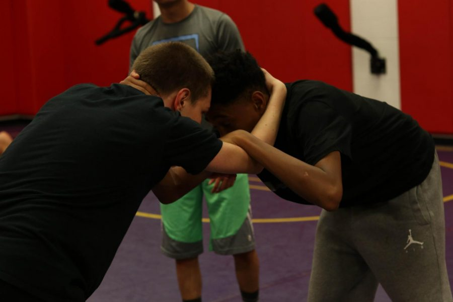 Senior Patrick Lynch (left) and sophomore Hurshawn Perkins (right) in a tie up during wrestling practice.