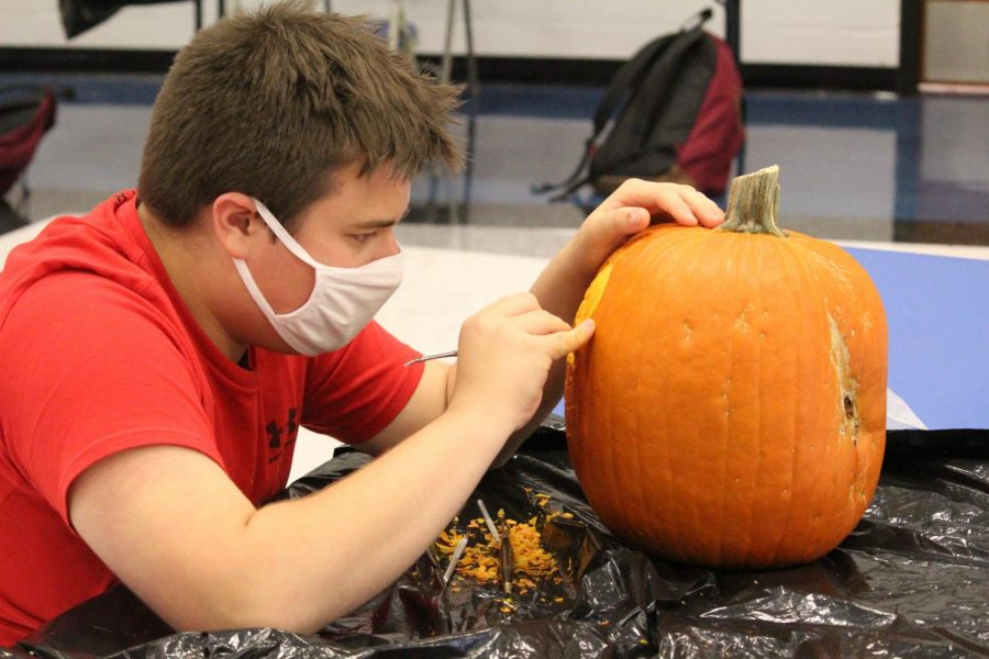 Andrew Taylor carves his pumpkin of Homer Simpson.