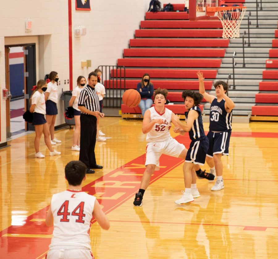 Aiden King (52) passes the ball to Carter Ashby in the JV basketball team's game against Timberland Dec. 8. The JV team lost a close game to the Wolves, 58-55.