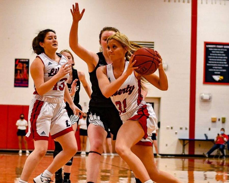 Hailey+Jolliff+drives+past+a+Orchard+Farm+defender+on+her+way+to+the+basket%2C+while+Ally+Schneipp+kicks.
