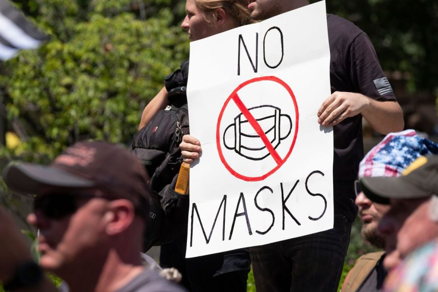 An anti-mask protester holds a sign in front of the Ohio Statehouse on July 18, 2020 in Columbus.