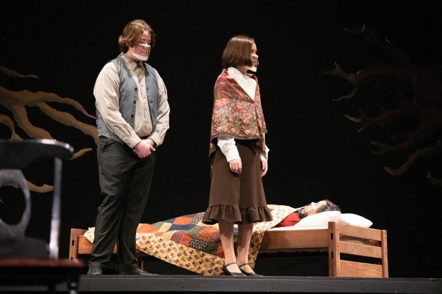 Thomas and Ann Putnam (Michael Gannon and Morgan Feinstein) observe the declining condition of the sick Betty Parris (Chynna Yeh).