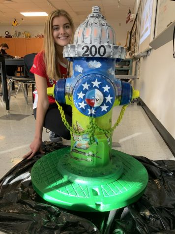 Kelly Karre poses with her fire hydrant that she painted.