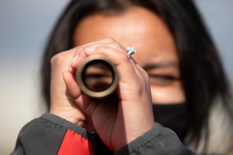 Sarah Merino (10) looks through a baton during at the Jefferson City track meet on Apr. 17.