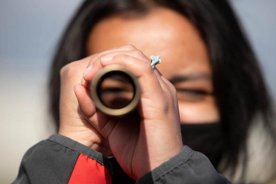 Sarah Merino (10) looks through a baton during at the Jefferson City track meet on Apr. 17.