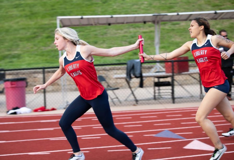 Karlie Wooten (9) has the baton passed on from Eve Shelton (12) during an exchange in the 4x400 relay.