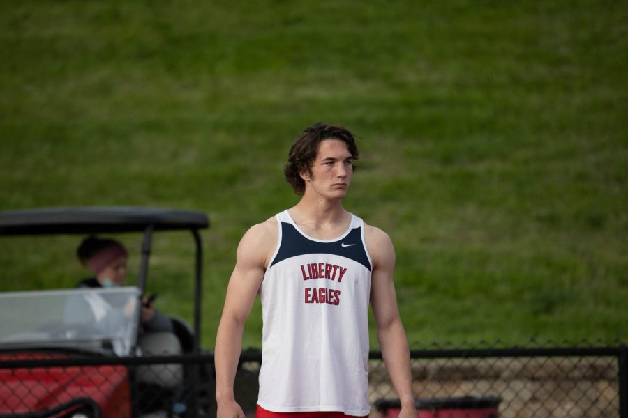 Wyatt Haynes (12) waits for the 4x400 to start so he can get ready to run.