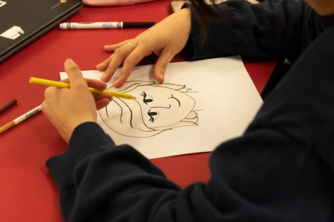 A student draws picture of Princess Diana, a woman who inspires her to hang on the bulletin board.