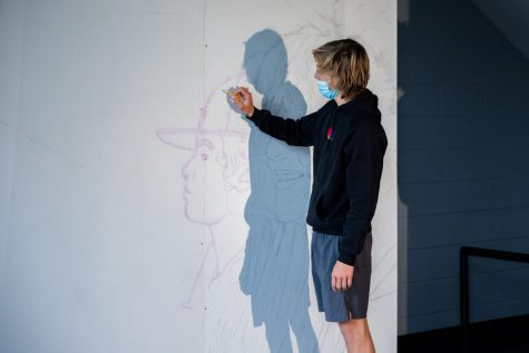 An art student works on a mural for Trotter to be used as a background for senior pictures.