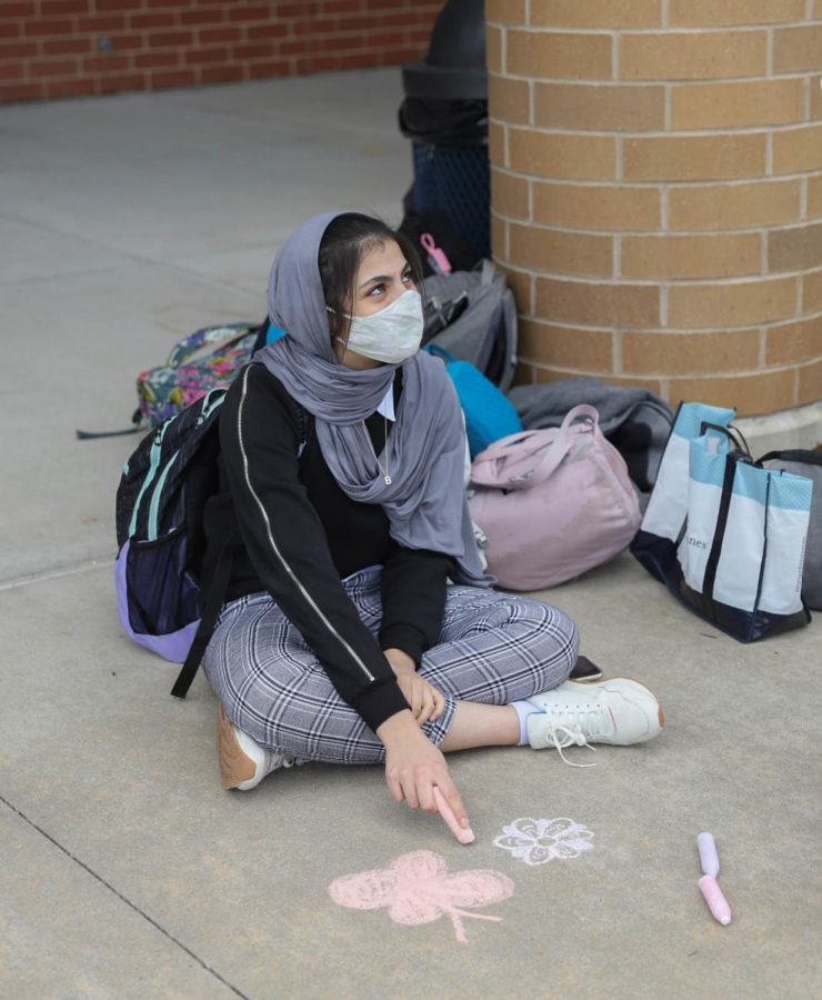 Saiya Ameen (9) talks to other club members as she decorates the sidewalk.