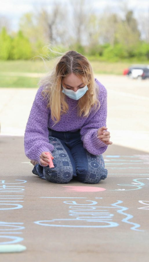Anna Wright (10) draws on the sidewalk in the front of the school.