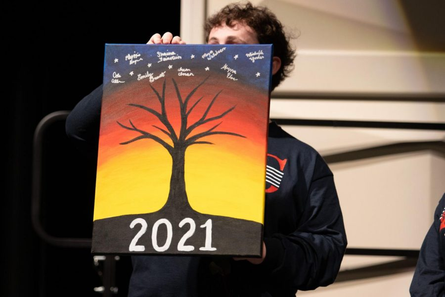 Cole Allen shows the audience the canvas that the senior choir students painted for Ms. Kennedy.