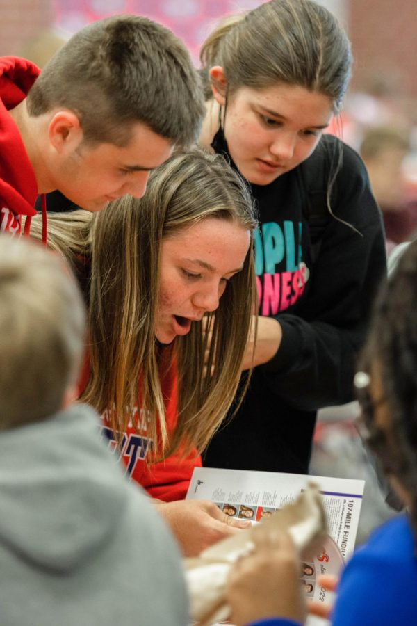 Students take their first look at the yearbook on distribution day.