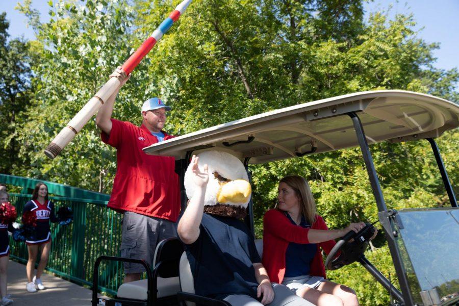 Coach Wheeler, Mr. Hill, and Dr. Kiely lead the bridge walk on a golf cart.