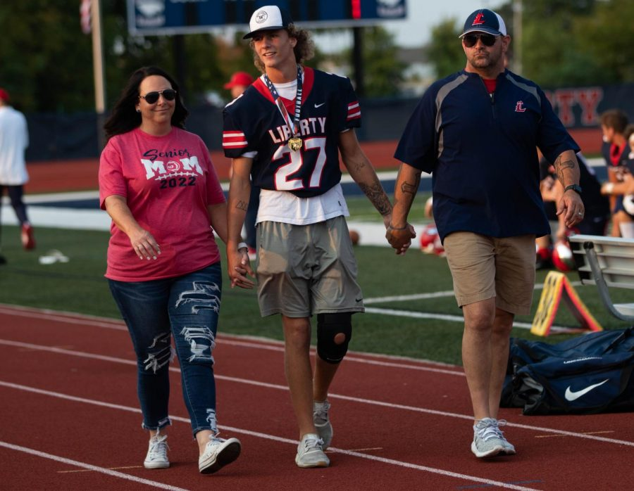 Colby Adelsberger holding hands while walking down the track with his parents, Erin and Jason.
