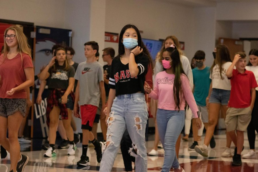 Masked+and+unmasked+Liberty+students+make+their+way+down+the+hallway.+