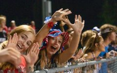 Seniors Maddie Ashlock and Anna Weber were showing their school spirit by holding up the Uncommon signal at the Warrenton game.