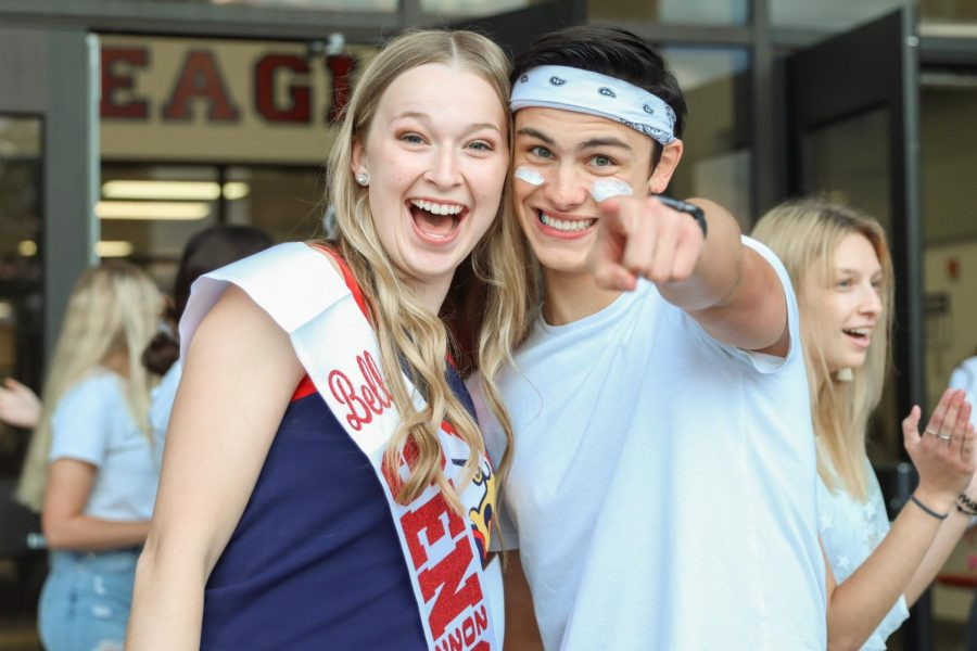 Student Council Vice President and President Bella Bahr (12) & Carson Clay (12) greet students before school for the White-Out game.