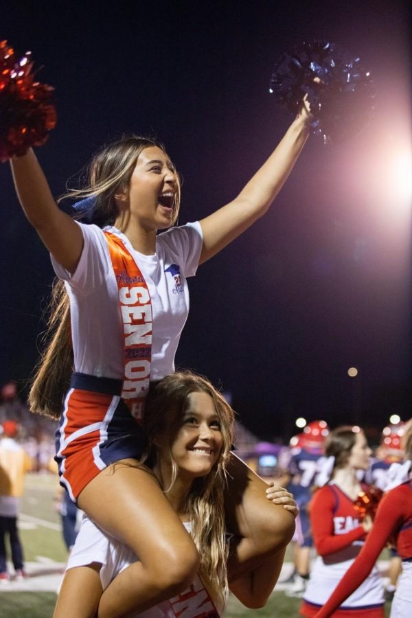 Senior cheerleaders Alana Clark and Rylee Gobble celebrate with the crowd during the football game.