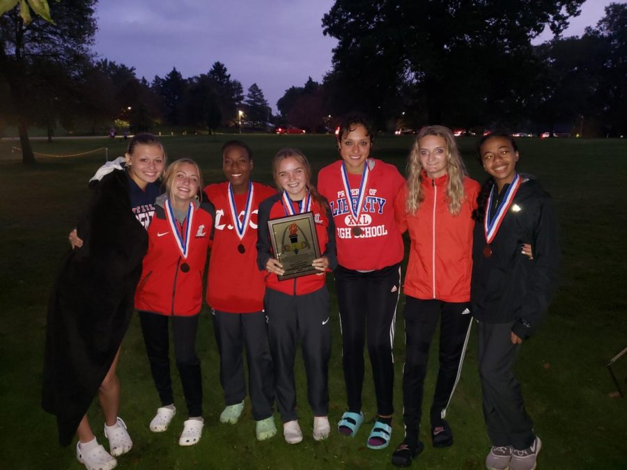 The varsity girls cross country team show their medals after winning conference at McNair Park. The runners were: Fiona Flynn, Jillian Kalbac, Leilani Green, Ally Kruger, Adrienne Rockette, Alexis Omara and Imane Larhdiri.