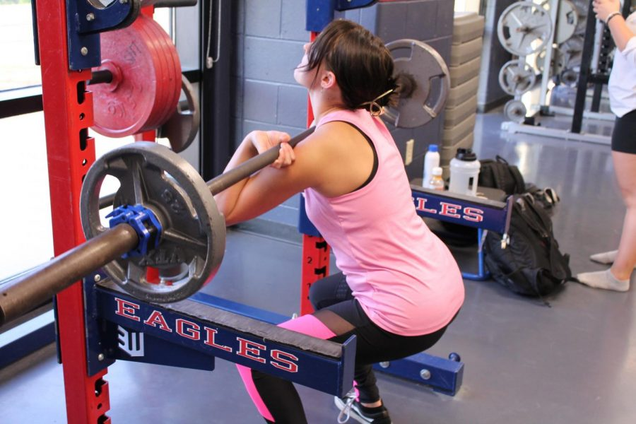 Kaytlee Thompson (12) gets in the eccentric phase of the front squat in weightlifting class.