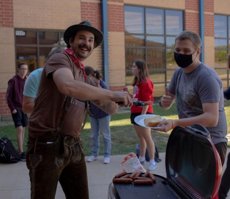 Herr Stoll poses with Ty Dalton as he serves the hot dog to his plate.