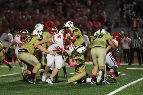 Senior Riley Laws pushes his way through the Lions defense to defend the ball.
